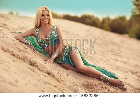 Beautidul smiling lady dancing Belly dance in the sands desert Blue dress