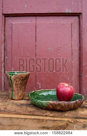Milk firing set of brown-green ceramic tableware brown-green ceramic on a red background red apple in a clay plate