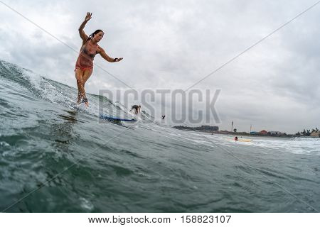 BALI, CHANGGU - NOVEMBER 25 2016: Young lady surfer catching the wave on the longboard
