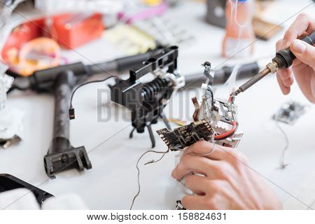 Energy and patience. Detailed close up of mans hands working with drone chips while soldering them and using soldering iron.