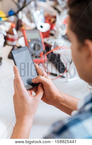 Type it. Close up of young mans hands using smartphone while sitting in workroom with electronic tester and other technical equipment lying on a table.