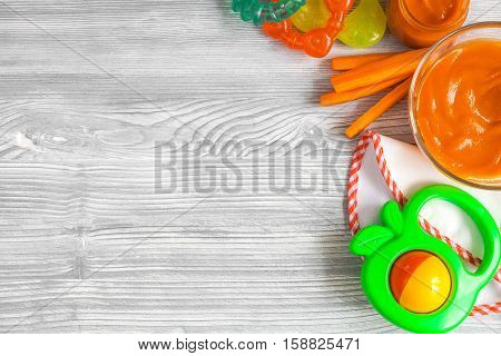 cooking mashed carrots for baby on wooden background top view.
