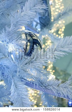Christmas decoration garland mirror ball and lights on the Christmas-tree with bokeh background. Modern style white blue shades. Artistic retouching. Contemporary art. Greeting card.