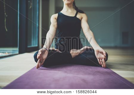 Portrait of happy young woman practicing yoga indoor. Beautiful girl practice relaxation asana in class.Calmness and relax, female happiness concept.Horizontal, blurred background