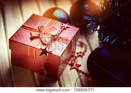 Christmas balls, bijouterie and gift box on a wooden background