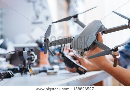 Use it properly. Close up of mans hands holding drone propeller and remore controller while testing the mechanism and sitting in a workroom.