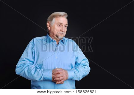 Keep your shirt on Portrait of good-looking man in years turning his head aside and keeping both hands on the stomach