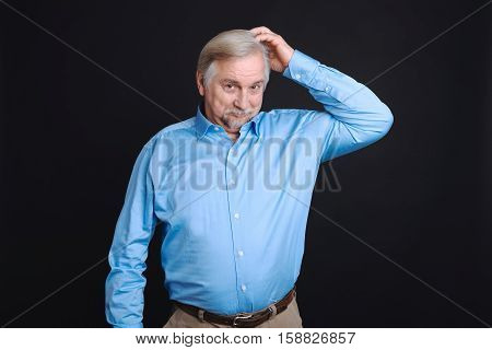 Good idea. Positive delighted enigmatical pensioner looking in camera scratching his head standing isolated on black background