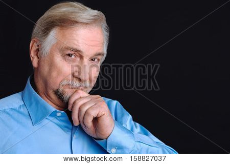 Have a point. Portrait of senior man smiling and loooking at camera keeping his hand on the beard, isolated on black background