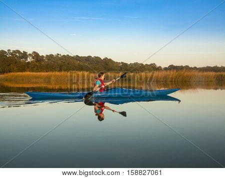 Teen girl paddling sea kayak through glassy water