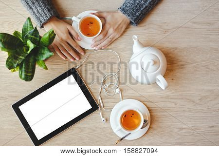 Girl sitting at the table and drinks green tea. Tablet with blank space and headphones lies nearby.