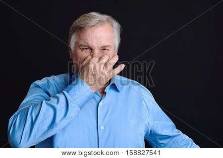 Feeling that unpleasant smell. Elderly man keeping his fingers on nose plugs looking at camera with disgust because of stink smell