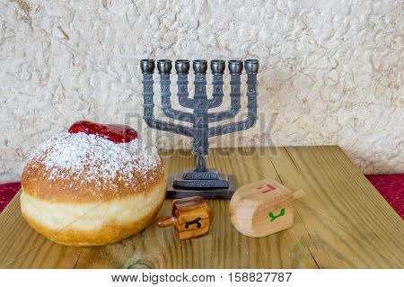 Festive sweet donuts, dreidels and menorah are traditional symbols of Hanukkah holiday
