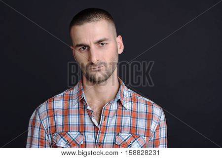 Your time is up. Handsome bossy man staring straight at camera wrinkling his forehead wearing checked shirt