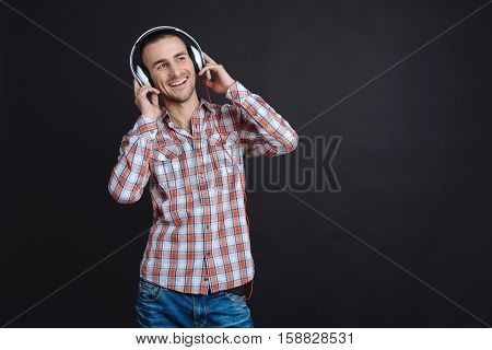 Time for music. Positive delighted brown-haired man posing with both hands holding on earphones while standing against black background