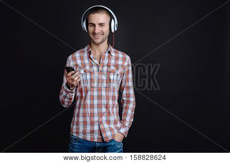 Good mood. Young handsome man holding phone in right hand and left hand in the pocket while listening to music standing against black background
