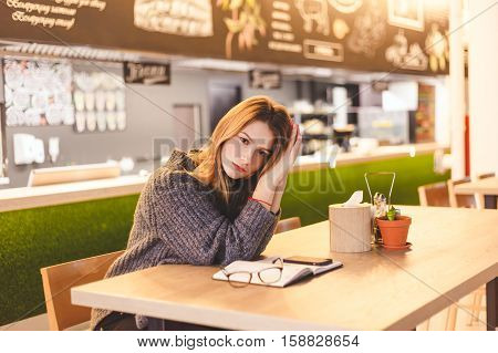 Young woman freelancer sitting in cafe after hard work day. Intelligent student rests in cafe after her lectures ends at University.