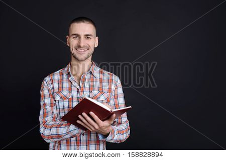 Study well. Positive delighted man holding brown book in both hands while reading wearing checked shirt, standing against black background