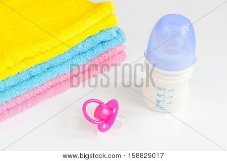 baby bottle with milk and towel on white background close up