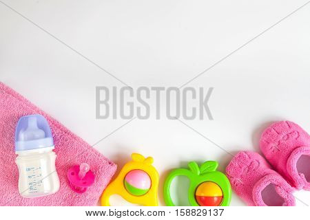 baby bottle with milk and towel, baby rattle, booties on white background top view