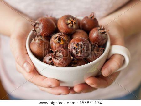 Women hands holding a white bowl full of medlar