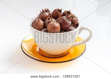 white bowl on a yellow saucer full of ripe medlar on a white background
