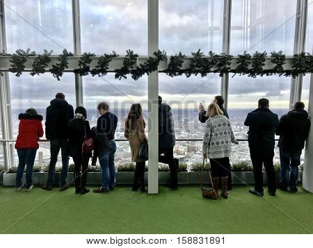 LONDON - NOVEMBER 27: People observing up to 40 miles away across the urban sprawl below from the outdoor gallery on level 72 of The View from The Shard on November 27, 2016 in London, UK.