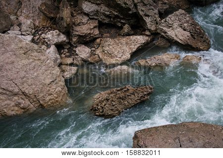 Landscape of rapid mountain river flowing between rough stones. Cold colors
