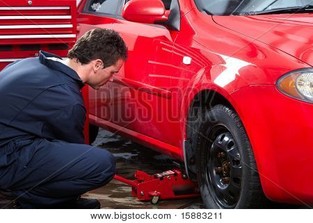 Handsome mechanic changing a tire. Auto service.