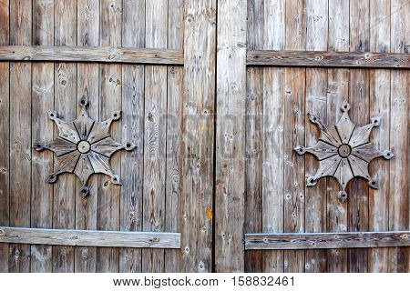 Fragment of closed old wooden gate with rusty hinges and traditional ornament
