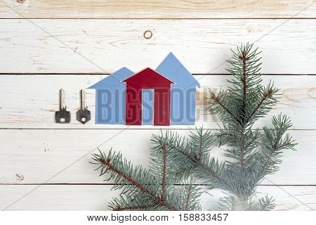 House and key on wooden background. Copy space for text.