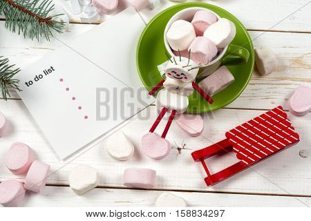 Christmas card with fun marshmallow snowman in green cup Christmas tree snow and sled. Copy space for text.