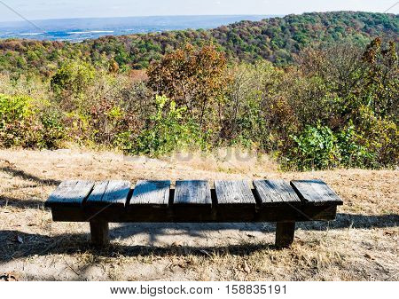 Park bench outdoors in fall with autumn colors changing on trees