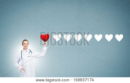 Young woman doctor against blue background holding red heart