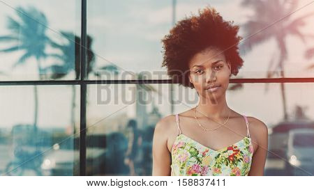 Portrait of young beautiful cute mixed brazilian teen girl with curly hair standing in front of tiled glass wall with reflections of palms and cars sunny summer day Rio de Janeiro brazil