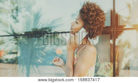 Portrait of black beautiful attractive young brazilian girl with curly hair in dress talking on smartphone standing in front of tiled glass wall with reflections of palms and cars sunny summer day