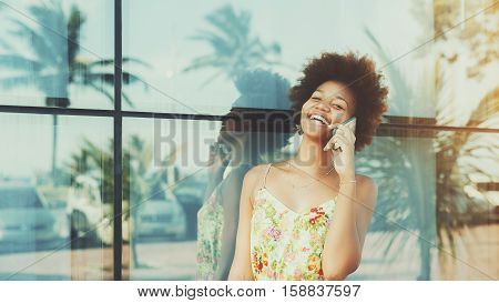 Black beautiful attractive young brazilian teen girl with curly hair in dress laughing while talking on smartphone standing in front of tiled glass wall with reflections of palms and cars sunny day