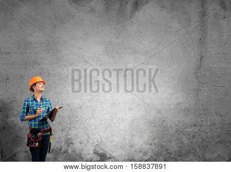 Engineer woman with folder against concrete wall background