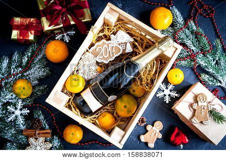 New Year's champagne and tangerines in box top view on dark background
