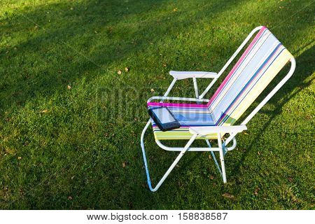 e-Book reader on the chair, green grass background