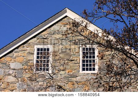 Two twelve over twelve window panes on the sunny side of an 18th century stone factory.