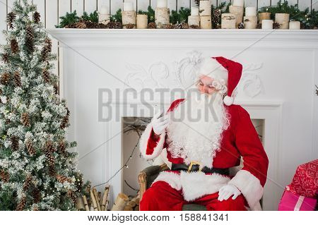 Happy Santa Claus typing a message on the mobile phone and smiling while sitting at his chair with fireplace. Christmas Tree in the background.