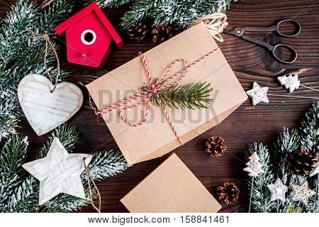 gifts boxes with fir branches on dark wooden background top view.
