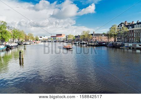embankments of Amstel canal with traditional houses in Amsterdam, Netherlands