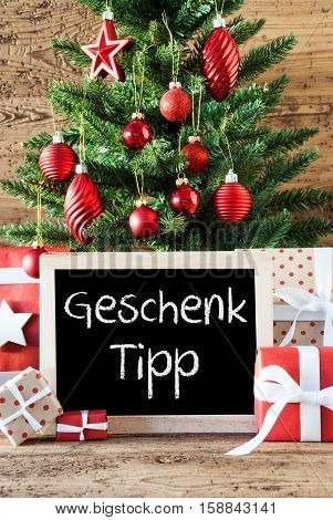 Chalkboard With German Text Geschenk Tipp Means Gift Tip. Colorful Christmas Card For Seasons Greetings. Christmas Tree With Balls. Gifts Or Presents In The Front Of Wooden Background.