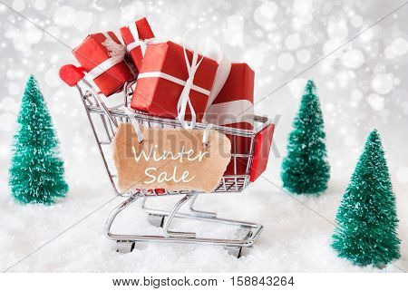 Trolley With Christmas Presents Or Gifts. Snowy Scenery With Snow And Trees. Sparkling Bokeh Effect. Label With English Text Winter Sale