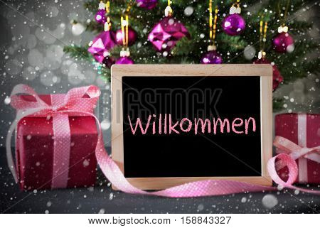 Chalkboard With German Text Willkommen Means Welcome. Christmas Tree With Rose Quartz Balls, Snowflakes And Bokeh Effect. Gifts Or Presents In The Front Of Cement Background.