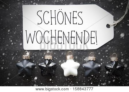 Label With German Text Schoenes Wochenende Means Happy Weekend. Black And White Christmas Tree Balls On Black Paper Background With Snowflakes. Christmas Decoration Or Texture. Flat Lay View