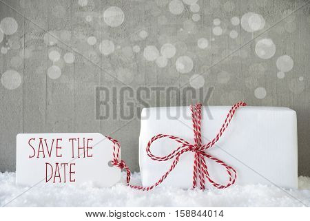 Label With English Text Save The Date. One Christmas Gift Or Present On Snow. Cement Wall As Background With Bokeh. Modern And Urban Style.