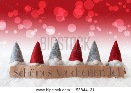 Label With German Text Schoenes Wochenende Means Happy Weekend. Christmas Greeting Card With Red Gnomes. Bokeh And Christmassy Background With Snow.